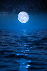 Full moon rising over empty ocean at night