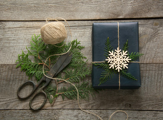 Christmas gift box wrapped in black paper with twine, branch cypress on wooden surface. Rustic style.