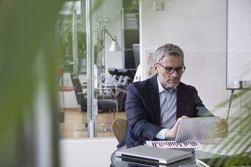 Successful businessman sitting in board room using digital tablet Wall mural