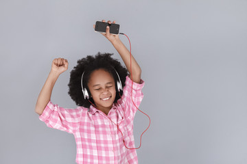 Dance! Little mulatto girl in headphones holding mobile phone and dancing with closed eyes on grey background