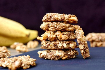 Wall Mural - Banana cookies with walnuts and oats on dark background