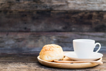 coffee mug with bread and wooden spoon on wooden table from above, breakfast, copy space on the left side