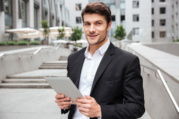 Attractive young businessman using tablet near business center Wall mural