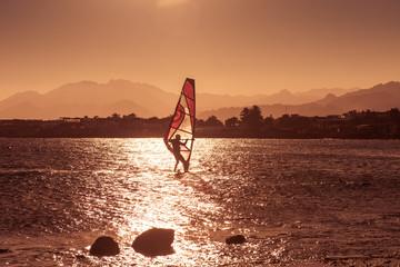 Windsurfer sailing in sea at sunset