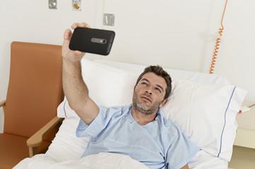 man lying on bed hospital clinic holding mobile phone taking self portrait selfie photo sad depressed