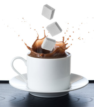Cup of coffee with falling sugar cube  isolated on white backgro