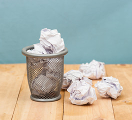 Recycle,trash bin and crumpled paper balls on wood