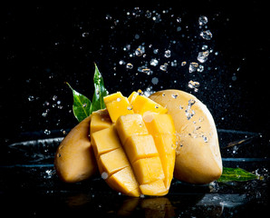 Mango splashing over clear water on black background
