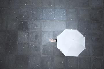 Top view of a woman hidden under white umbrella