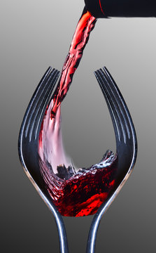 Wine and Dine. Two forks shaped like a wine glass with red wine being poured. Gray background.