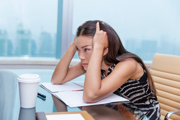 Stressed business woman at office desk stressing about work. Negative concept, headache, migraine. Tired businesswoman sitting thinking about problems and showing dissatisfaction of career.