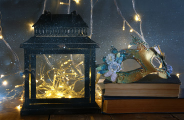 fairy lights inside old lantern and masquerade venetian mask