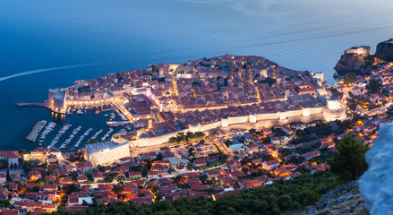 Lovely panoramic view of the old walled city of Dubrovnik with bird's eye view at night. City backlit. Croatia