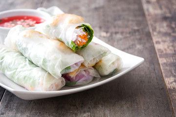 Vietnamese rolls with vegetables, rice noodles and prawns with sweet chili sauce  on wooden background