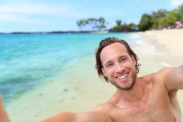Beach holiday man taking selfie on travel vacation. Handsome young guy smiling at camera for self-portrait picture with smartphone on summer getaway. Happy tropical travel destination.