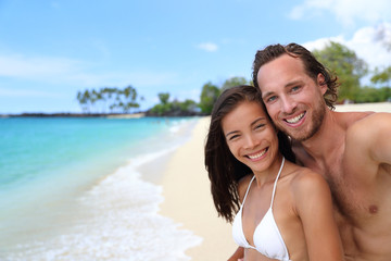 Happy couple selfie on exotic beach vacation. Beautiful interracial young adults smiling taking a self-portrait photo with mobile phone on tropical travel destination with turquoise ocean background.