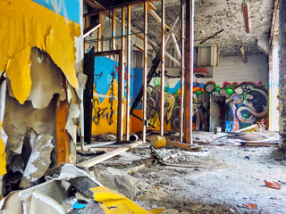 Destroyed building interior with smashed drywall and graffiti