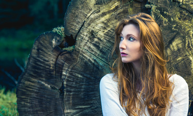 Thoughtful redhead woman resting against a fallen tree trunk