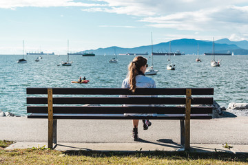 Girl Sitting on a Bench at Kitsilano Beach in Vancouver, Canada