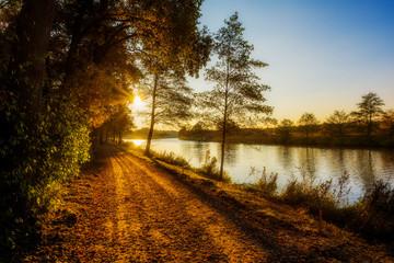 Landschaft im Herbst an einem Fluss bei Sonnenuntergang