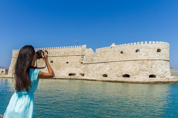 Young stylish woman photographing Rocca A Mare Heraklion, Crete,