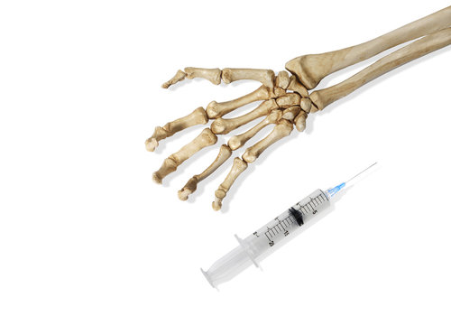 Skeleton Hand and a Medical Hypodermic Needle on a White Background