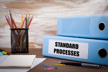 Standard Processes, Office Binder on Wooden Desk. On the table c