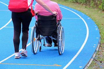 handicapped person on a wheelchair with an aide on the athletic