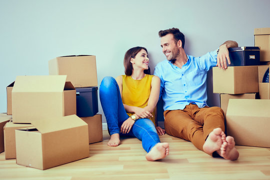 Happy couple having break during moving to new house