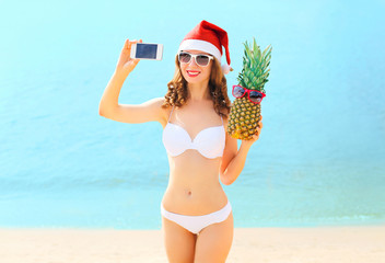 Christmas young smiling woman in red santa hat with pineapple ta