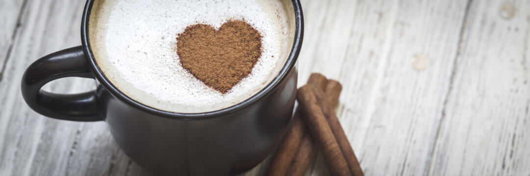 Coffee with cinnamon sticks and heart shape
