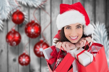 Beautiful woman in santa hat holding bags with gifts