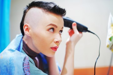 Young attractive girl shaves her hair on her head.