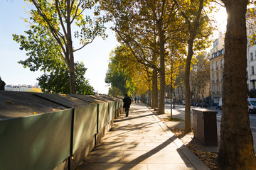 Golden silhouette style, walking along the road and closing book store in Paris during the sunrise in Autumn