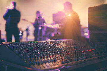 Soundman working on the mixing console in concert hall.