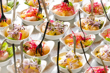 Colorful mini snacks, appetizers in white cups. Healthy diet or