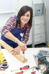 smiling woman assembling wooden planks using screwdriver