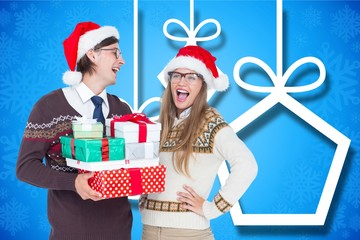 Happy couple in santa hat holding christmas gifts