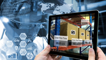 Industry 4.0 , Augmented reality and smart logistic concept. Hand holding tablet with AR application for check order pick time in smart factory.Man use AR glasses and industry infographic background. Fotoväggar