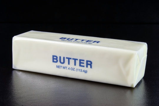Stick of butter. Black background. Horizontal.