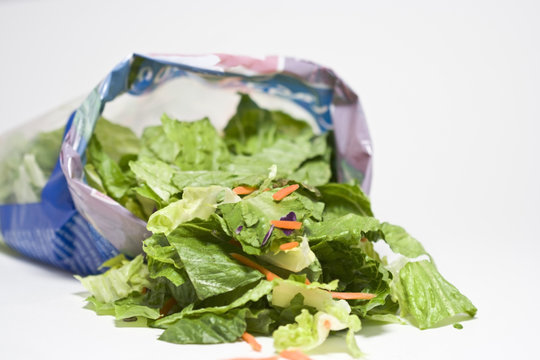 Open bag of salad. Lettuce and carrots. Shallow focus. White background. Horizontal.