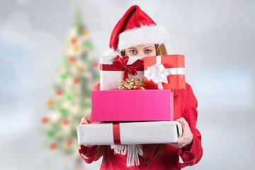 Woman in santa hat holding stack of gifts