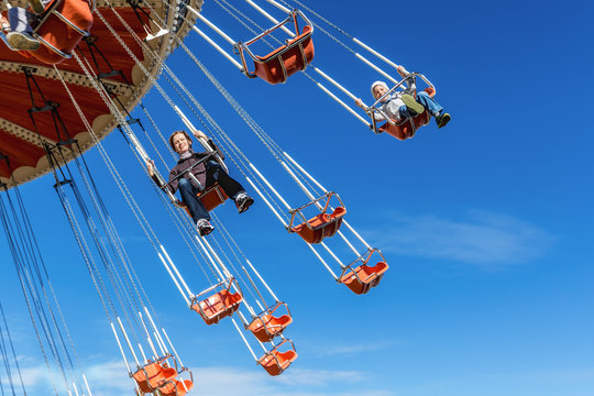Mother with the six-year-old son ride an attraction on a swing agains the blue sky in amusement park