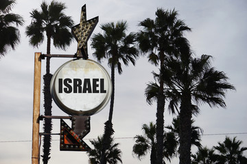 aged and worn vintage photo of israel sign with palm trees