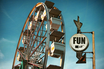 aged and worn vintage photo of ferris wheel with fun sign