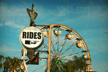 aged and worn vintage photo of ferris wheel with rides sign