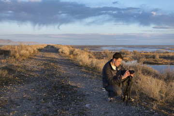 man taking pictures of the sunrise on the great salt lake