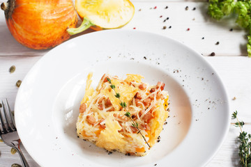 Rice casserole in cheese basket on plate. Tasty baked mix of rice and pumpkin with cheese. Restaurant food, seasonal menu, autumn cuisine concept