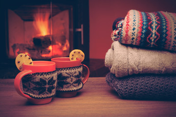 Cup with Christmas ornament near fireplace. Mug in red knitted cloth
