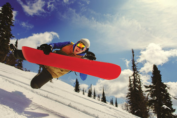 Snowboarder jumping through air with snowbord